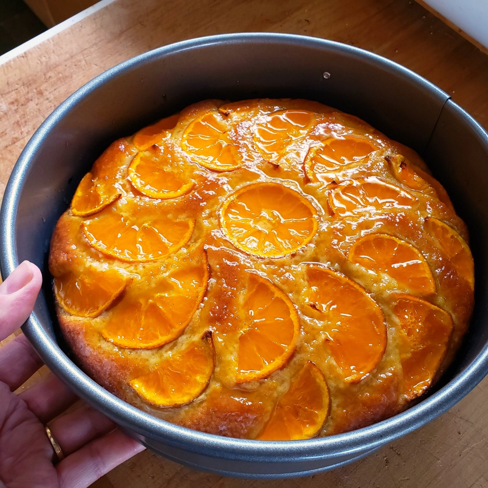 Glazed tangerine cake in a pan held by a hand