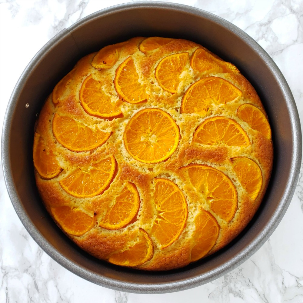Baked cake in a gray pan is out of the oven and on a white marble counter