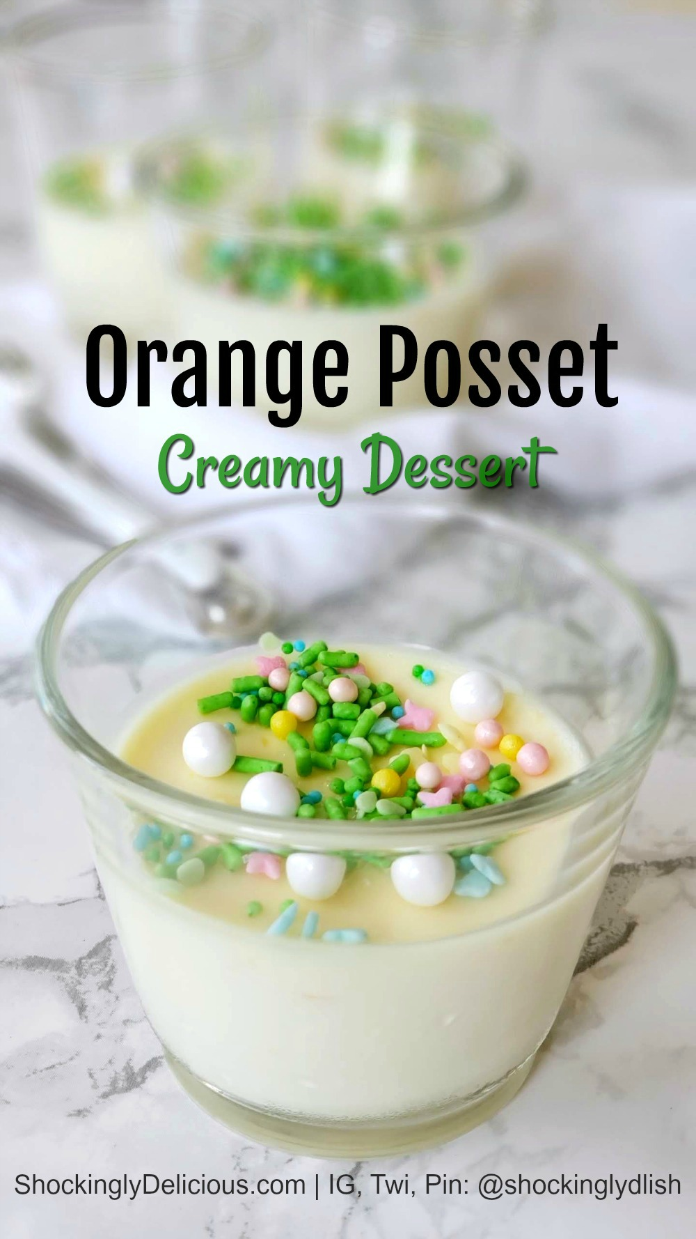 Orange Posset cup with sprinkles on top on a white marble counter