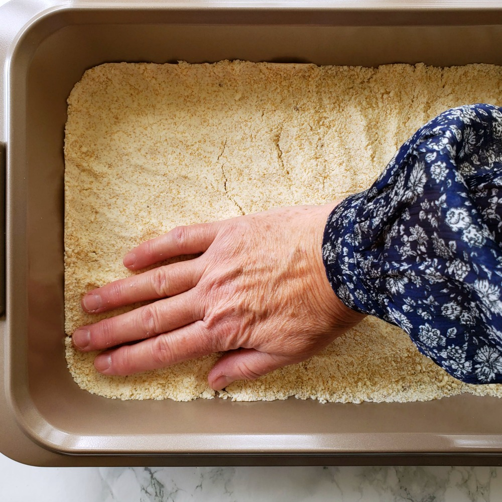A hand pats crust into a baking pan