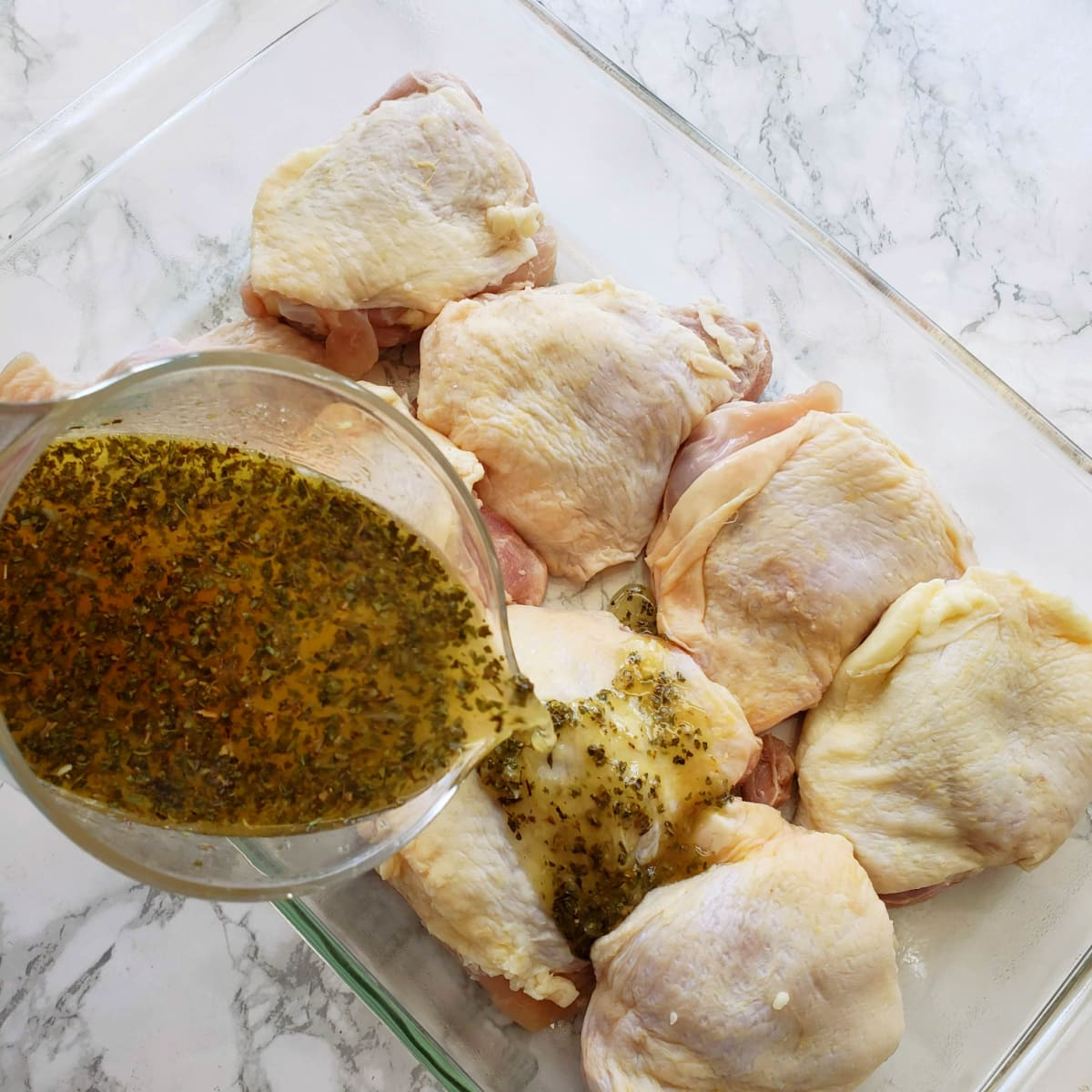 8 chicken thighs in a baking dish with marinade pouring over, set on a white marble counter