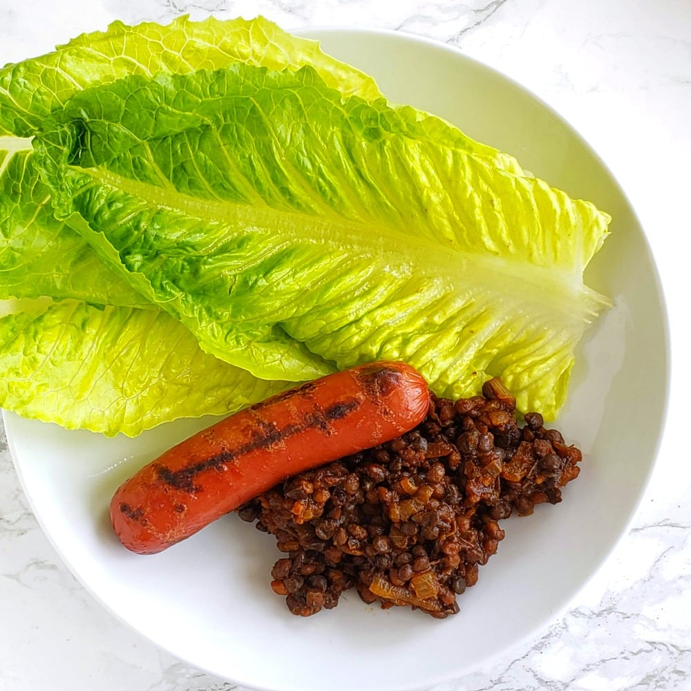 Barbecue Baked Lentils with a grilled hot dog and 3 spears Romaine lettuce in a white bowl