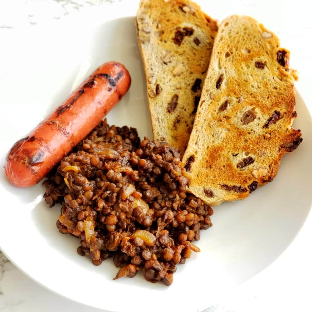 Barbecue Baked Lentils with grilled hot dog in a white bowl