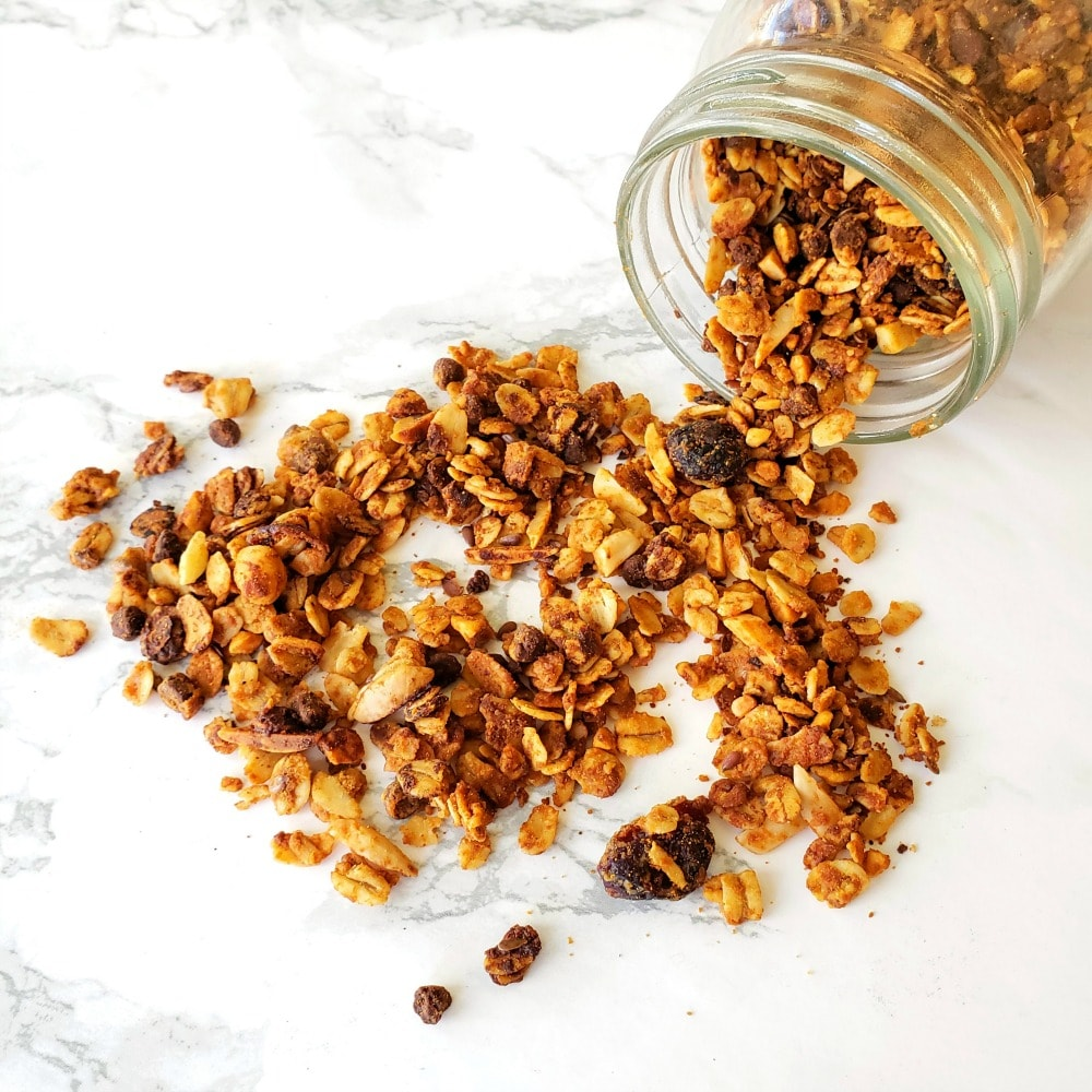 Honey Nut Granola spilling out of a jar on a white countertop