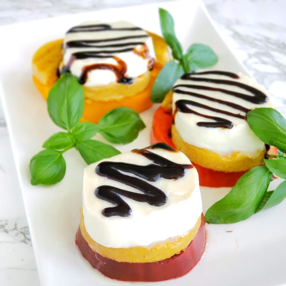 Polenta Caprese Stackers is a creative twist on a classic caprese salad, with cornmeal polenta adding a chewy layer as a counterpoint to the juicy tomato, creamy mozzarella and herbal basil.