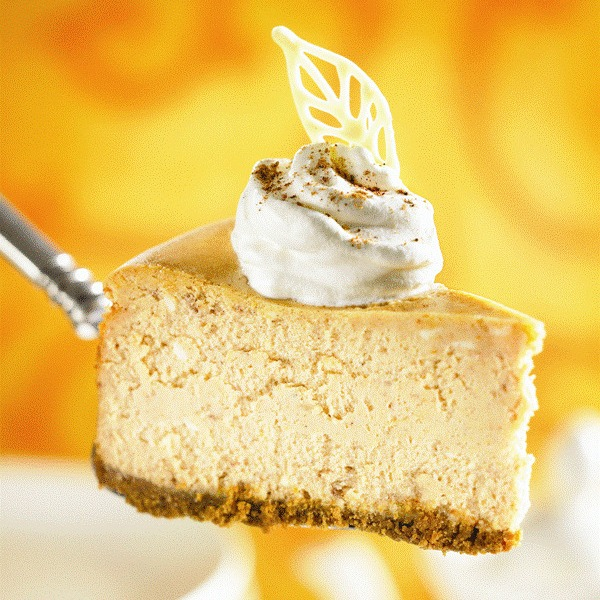 Sl;ice of Maple Pumpkin Cheesecake on a silver pie server with an orange background