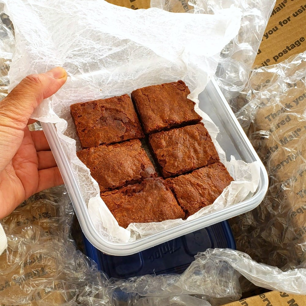 Fudgy Chocolate Brownies packed into a plastic container for shipping