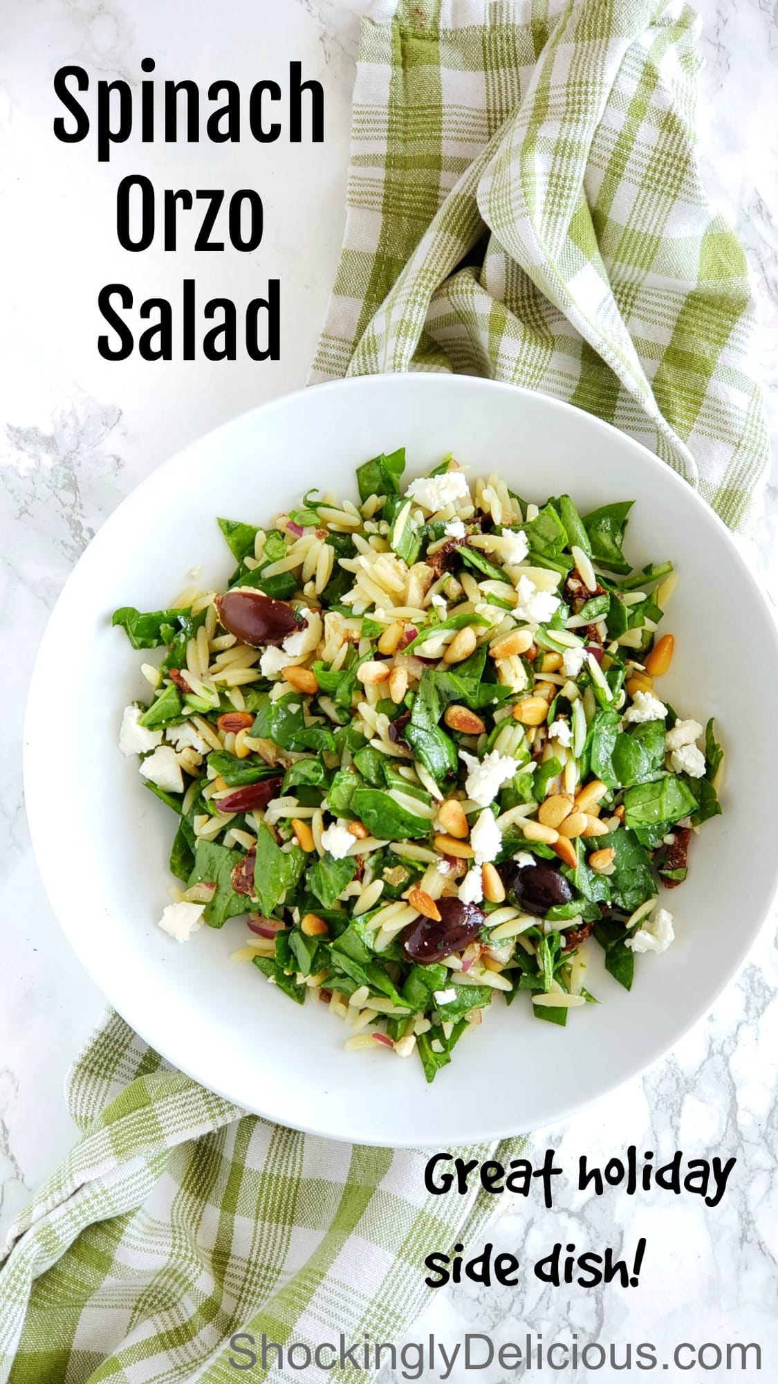 Easy Spinach Orzo Salad in a white bowl sitting on a green plaid dish towel on ShockinglyDelicious.com