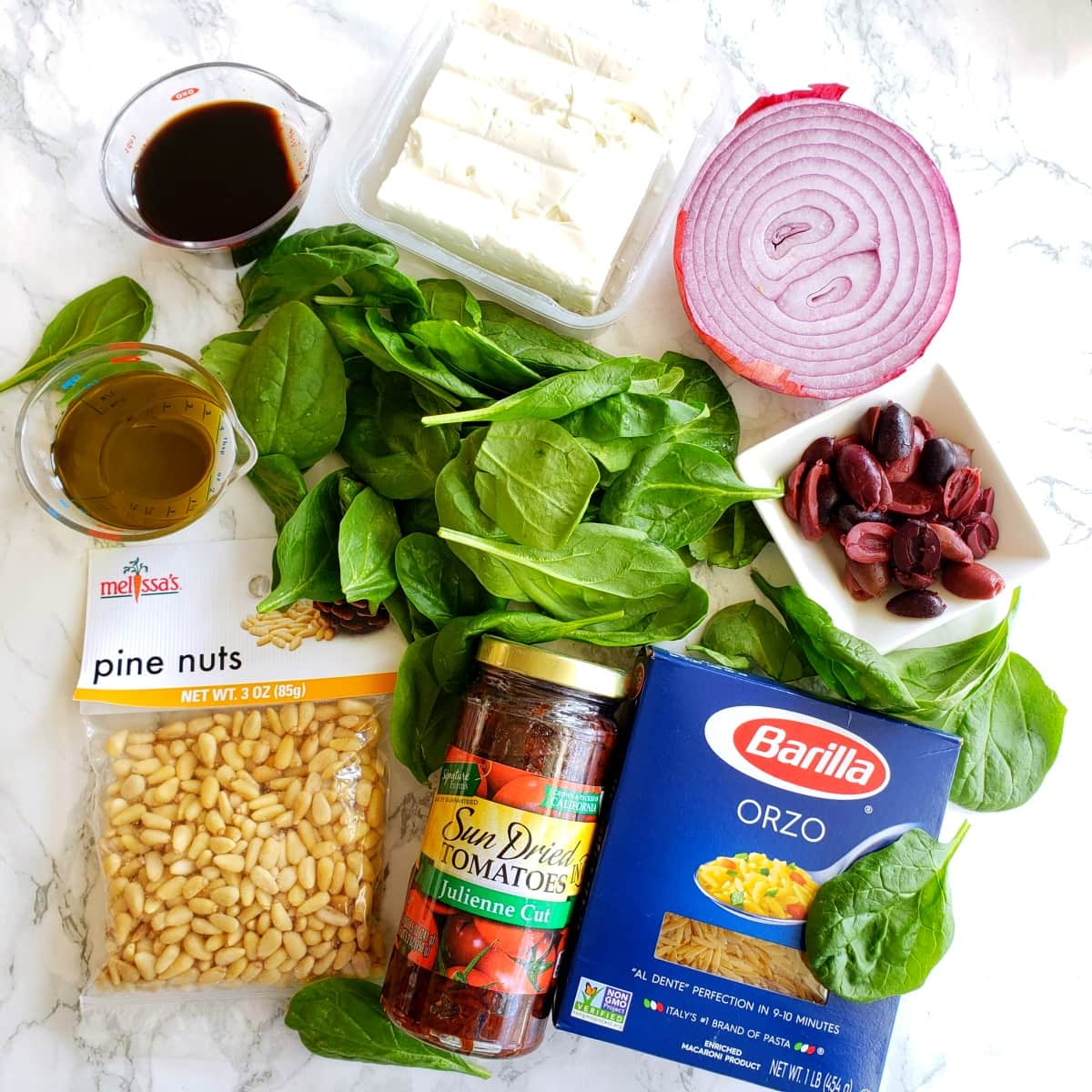 Ingredients for Spinach Orzo Salad on a white marble counter