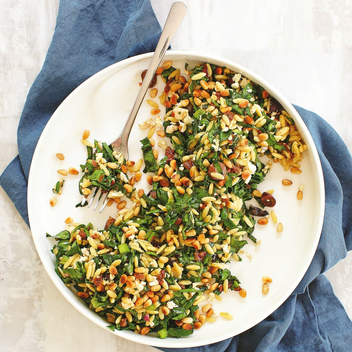 Spinach Orzo Salad is a fast, easy, delicious spinachy side salad chock full of salty feta and olives, flavorful sun-dried tomatoes and toasted pine nuts. Add cooked chopped chicken or another protein to make this a main meal.
