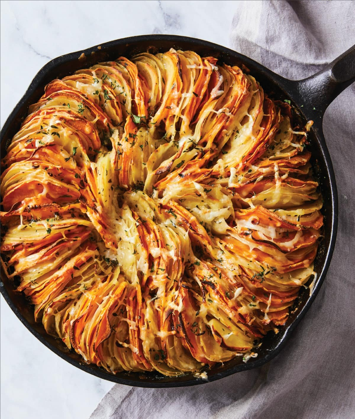 Cheese Herb Potato Gratin is the impressive side dish you'll want for the holidays, but can eat all year long. Impossibly thin leaves of potatoes stack sideways in a skillet with herbs and cheese for a deeply satisfying, comforting dish.