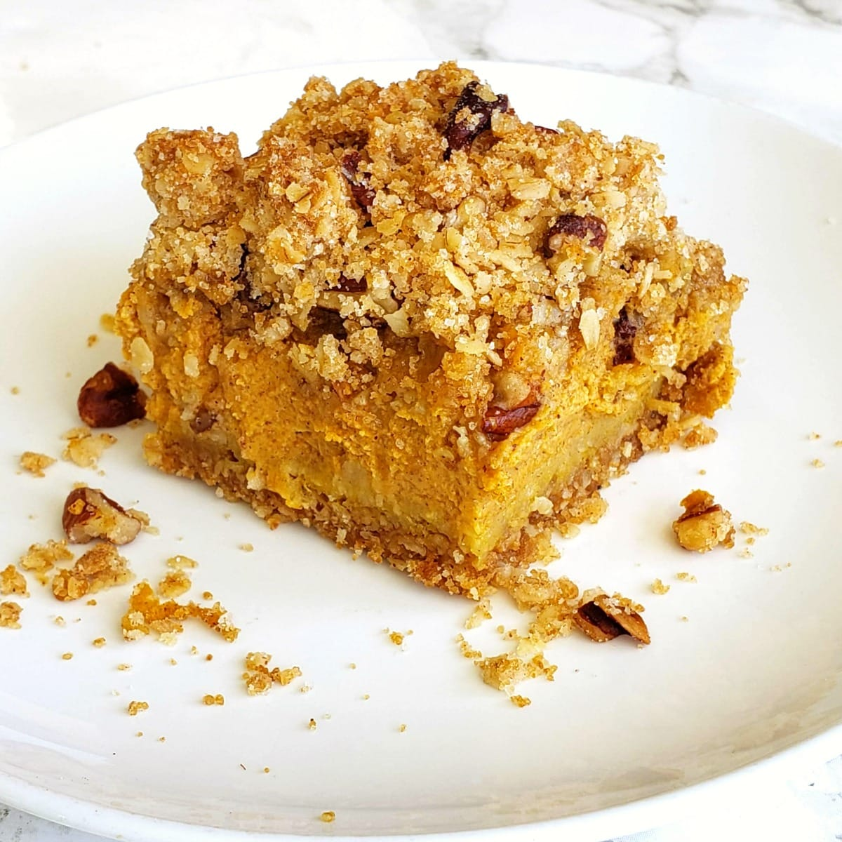 Pumpkin Pie Bars with Oat Crumble Topping on a white plate on a marble counter