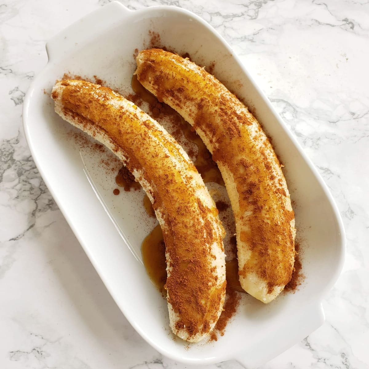 2 Bananas in a white baking dish with maple and cinnamon on top