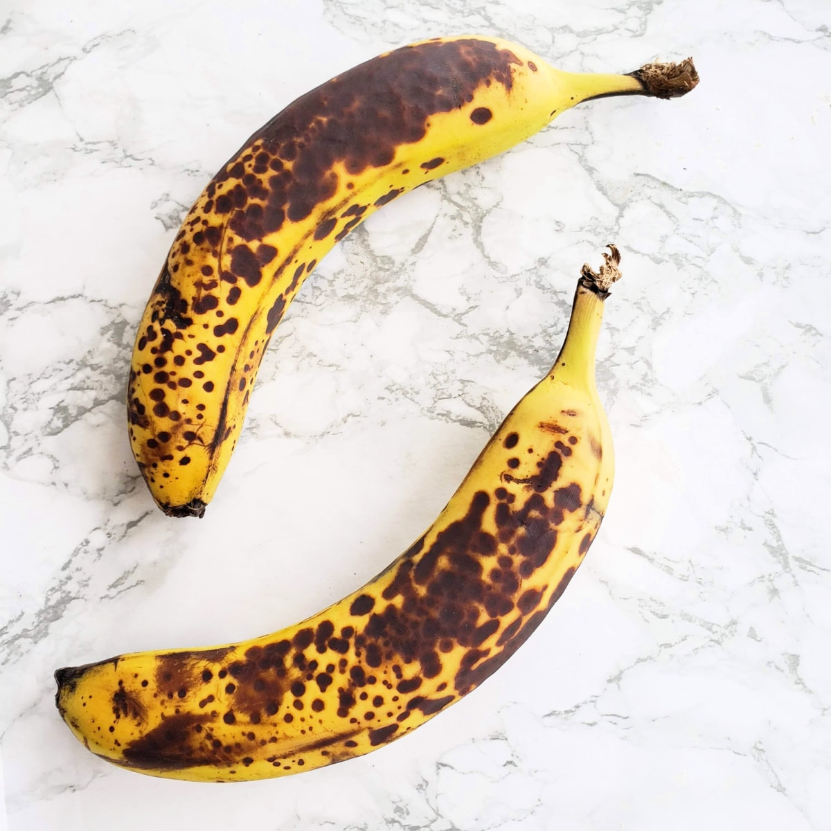 2 speckled ripe bananas on a white marble counter on ShockinglyDelicious.com