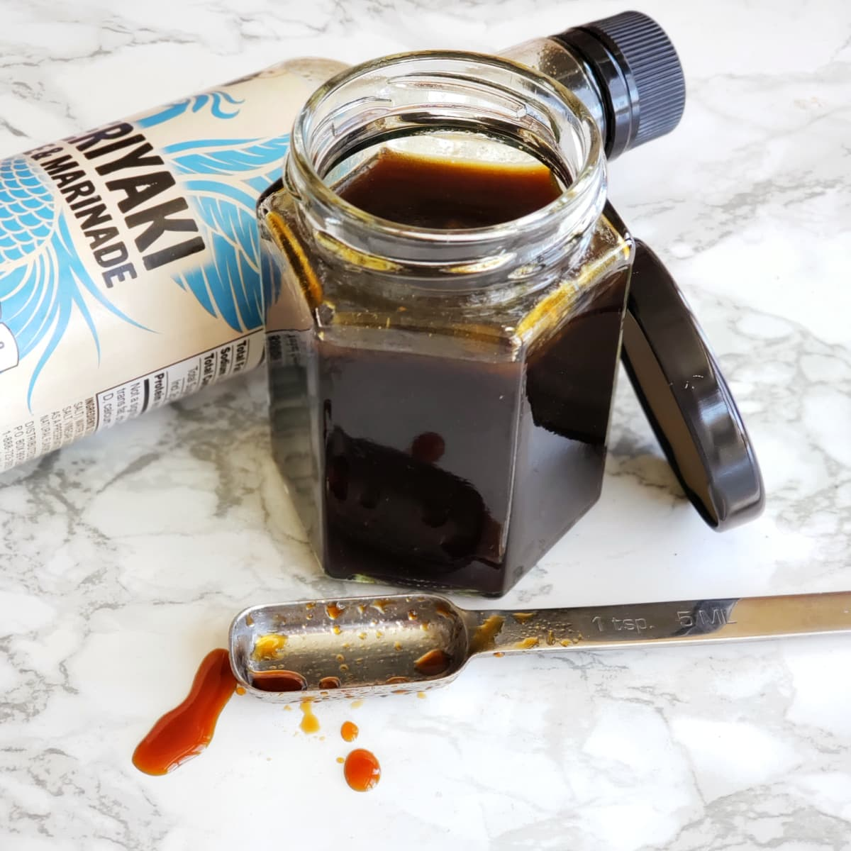 Homemade Teriyaki Sauce in a six-sided glass jar on a white marble counter on ShockinglyDelicious.com
