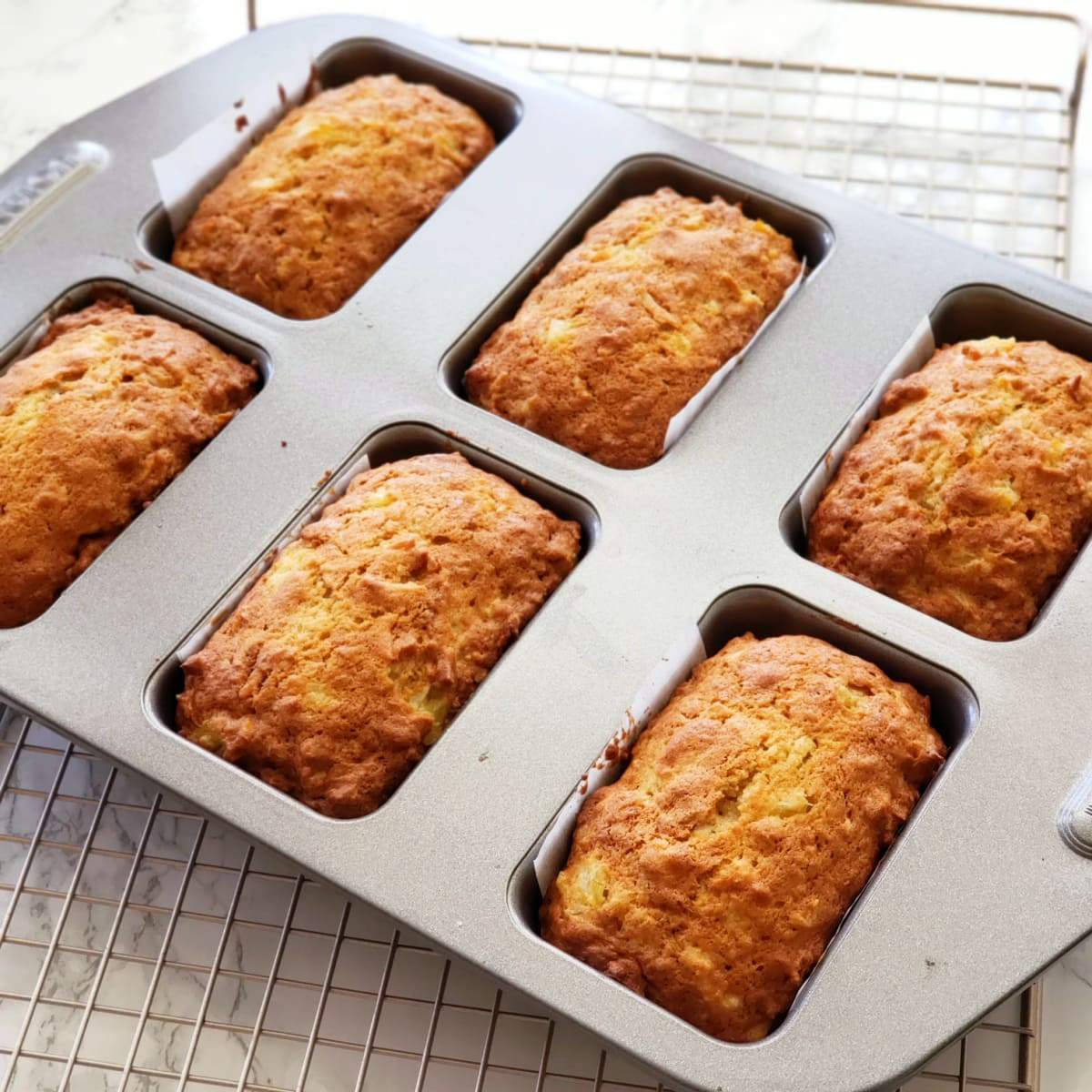 6 Baked loaves in the silver mini loaf pan on a wire rack