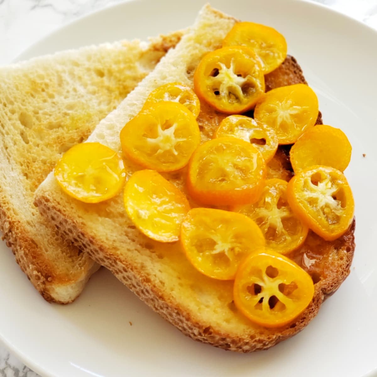 Candied Kumquats on sourdough toast on a white plate