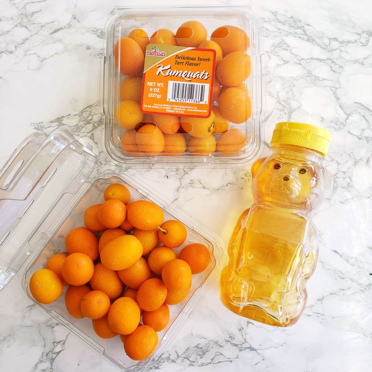 Kumquats and honey on a white marble counter
