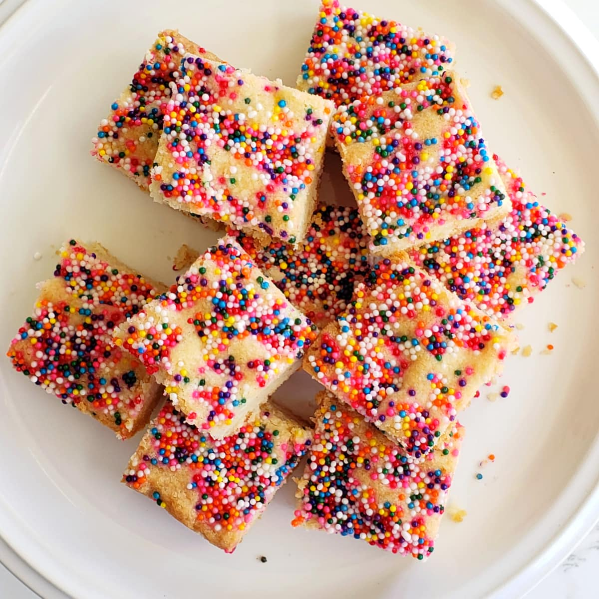 Simple Lemon Shortbread with Sprinkles piled on a white plate on ShockinglyDelicious.com