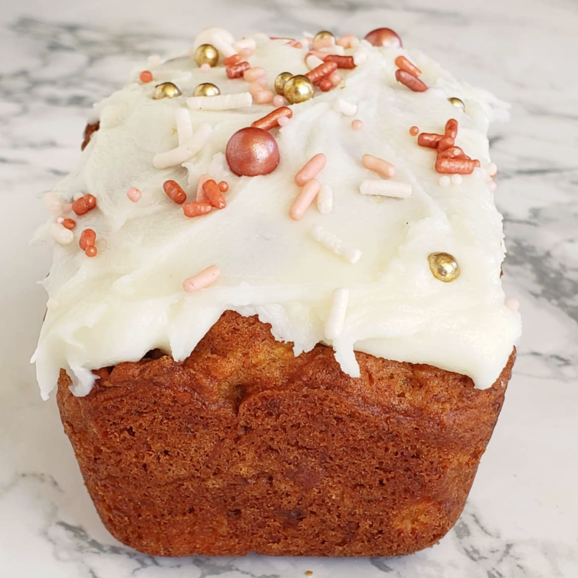 Simple Pineapple Coconut Quick Bread with frosting and sprinkles on a white marble counter