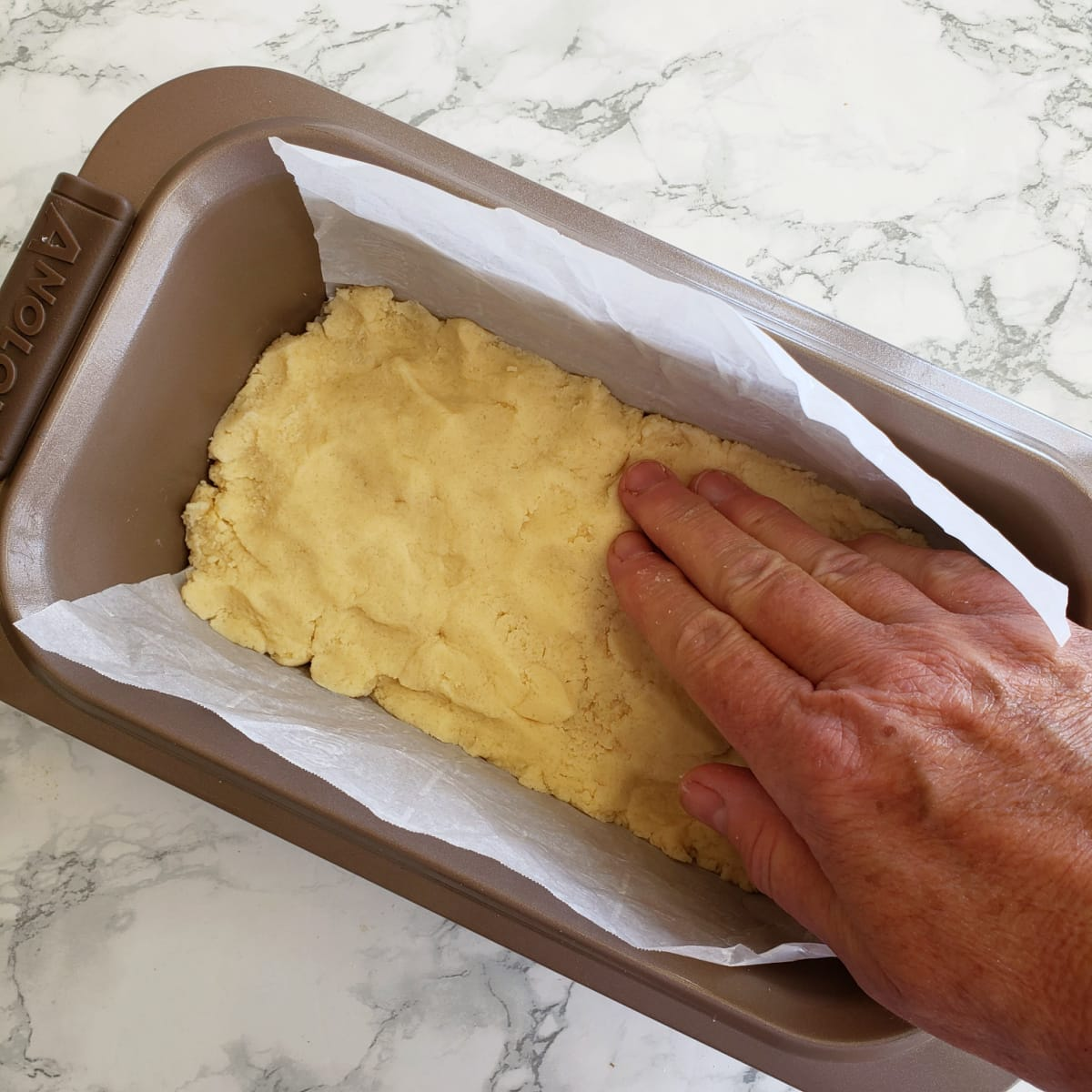 Use your hand to press the shortbread dough into the pan