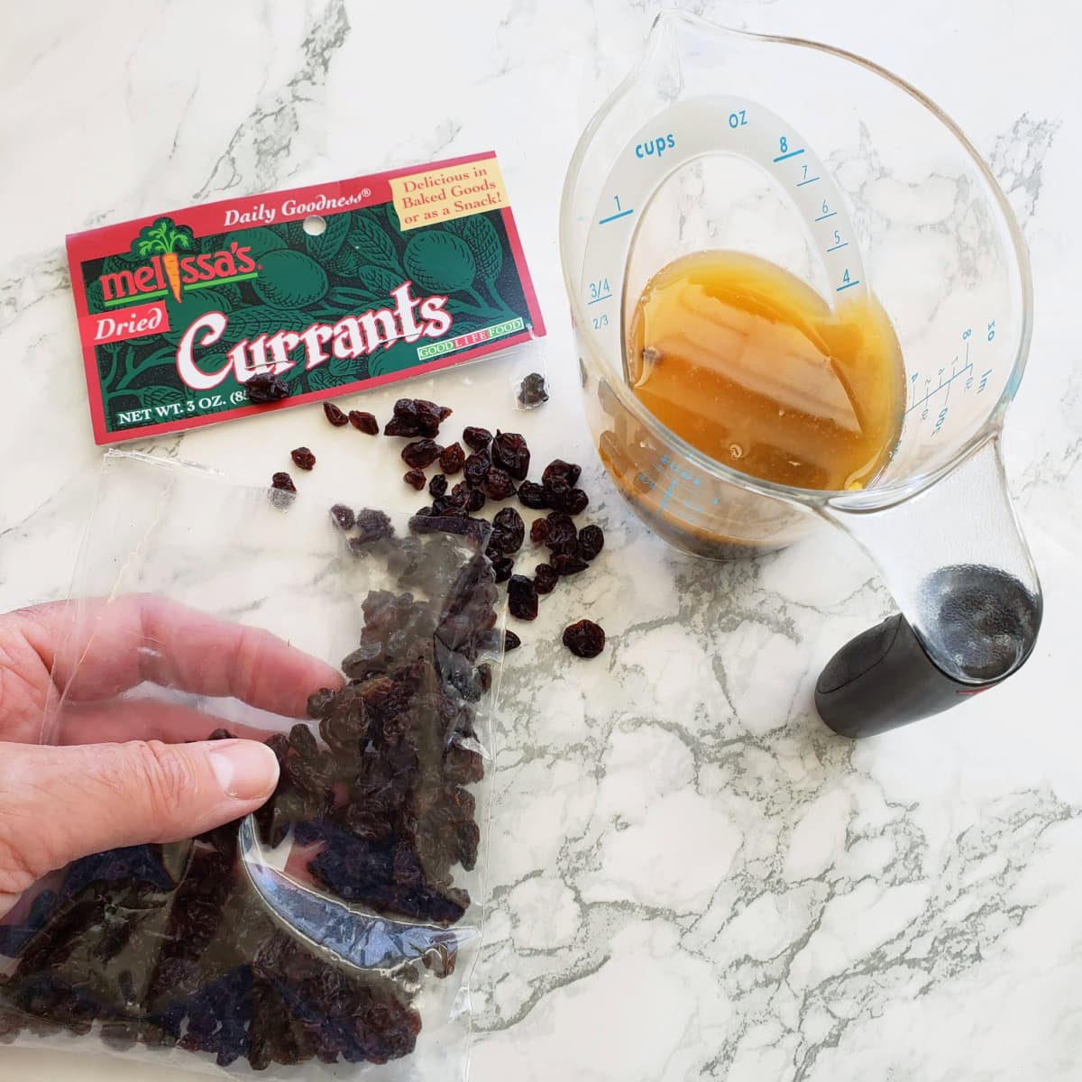Currants will soak in tangerine juice in a measuring cup on a white marble counter