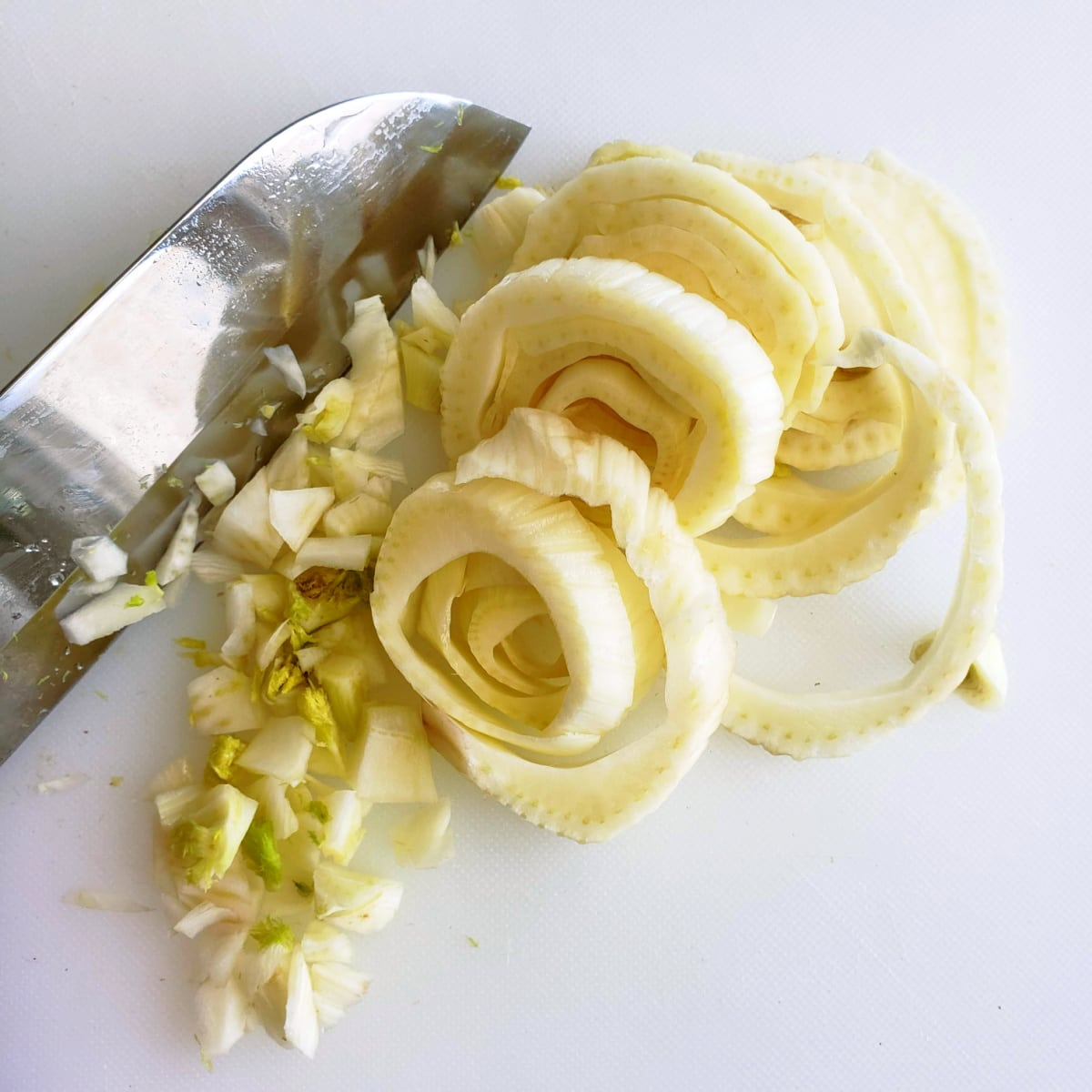 Cut fennel into rounds with a knife on a white cutting board