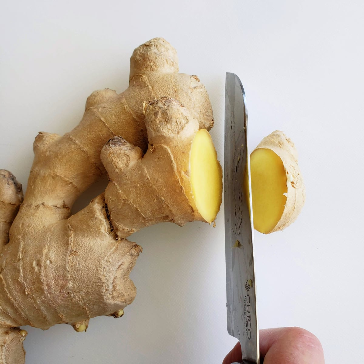 Cut ginger into coins on a white cutting board