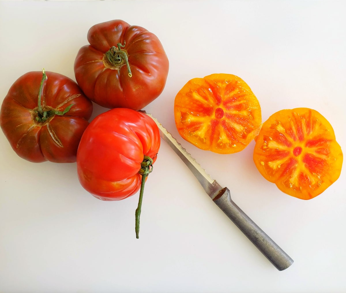Heirloom tomatoes on a white cutting board with a knife