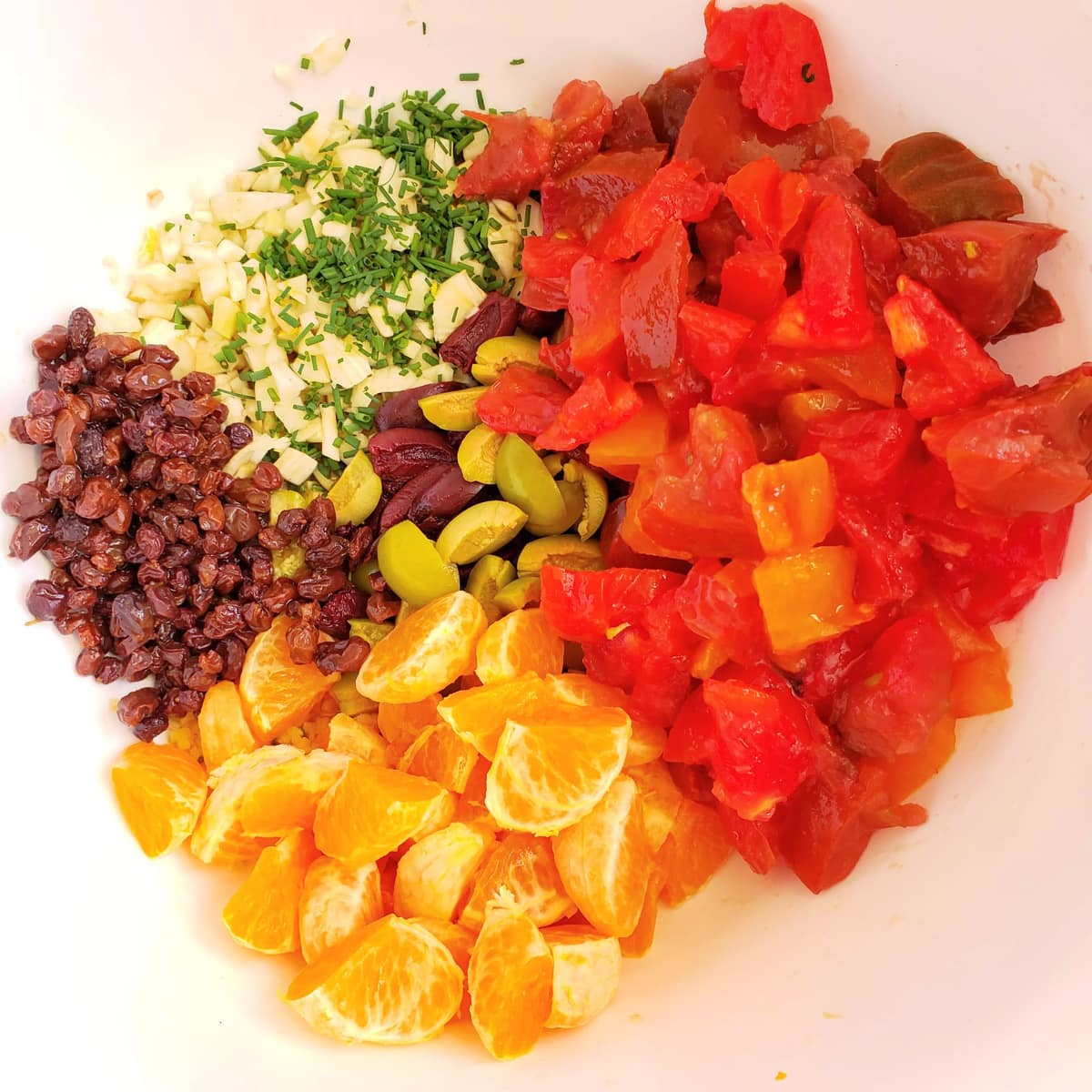 Toss the vegetables and fruits for Pasta with Tomatoes and Tangerines into a white mixing bowl