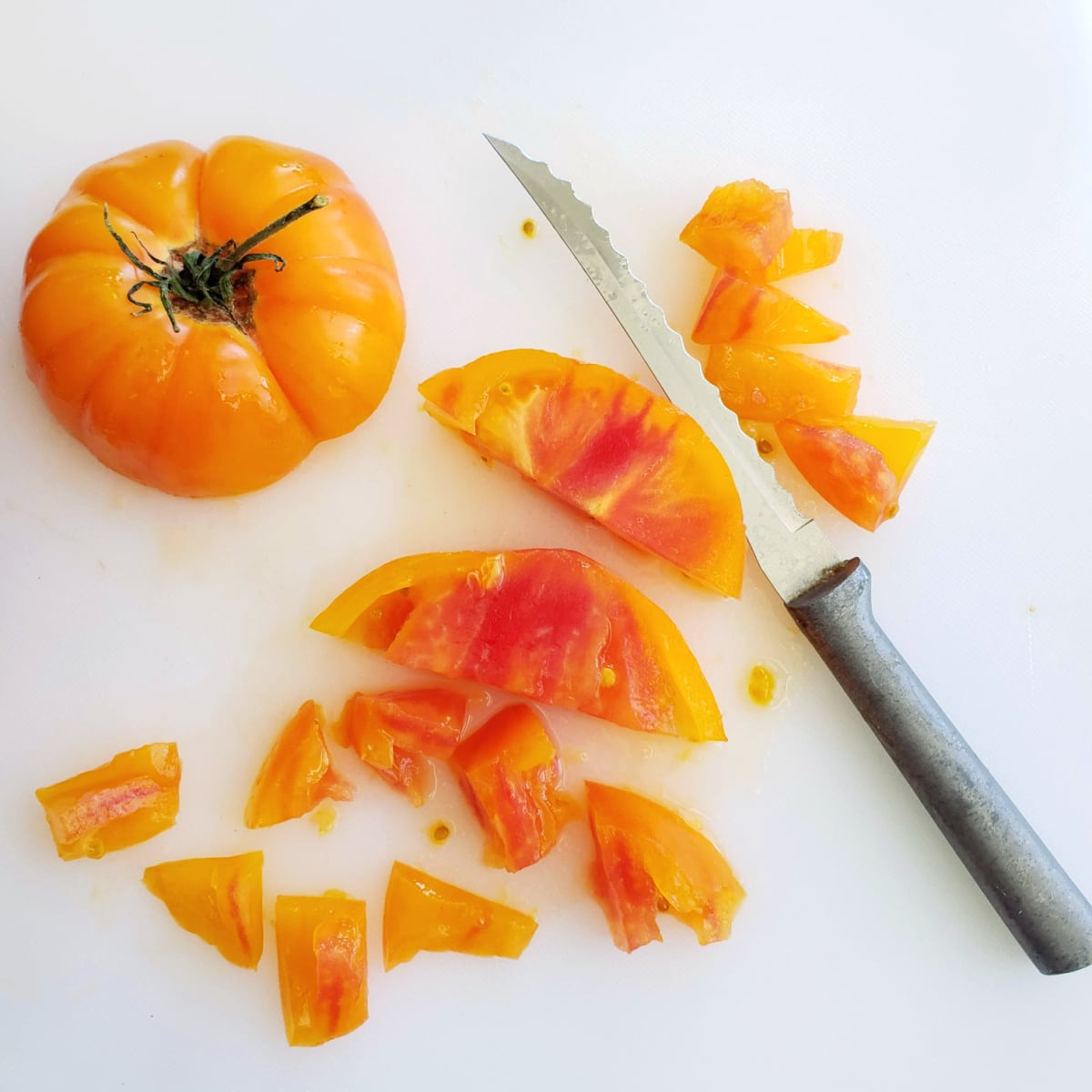Yellow heirloom tomato on a white cutting board with a knife