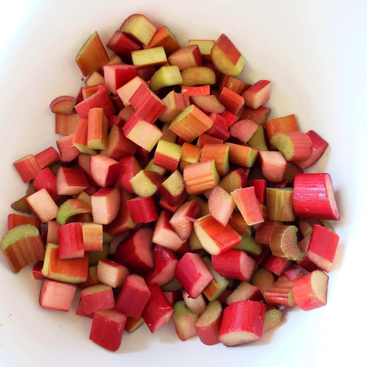 Bright red and green chopped rhubarb in a white mixing bowl on ShockinglyDelicious.com
