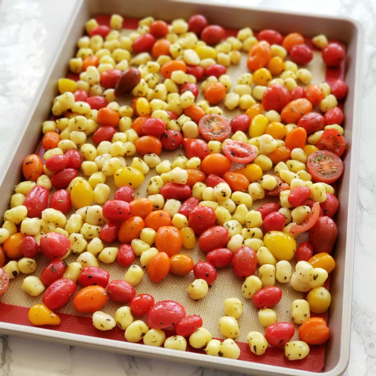 Gnocchi and tomatoes on a gold colored sheet pan on a white marble counter on ShockinglyDelicious.com