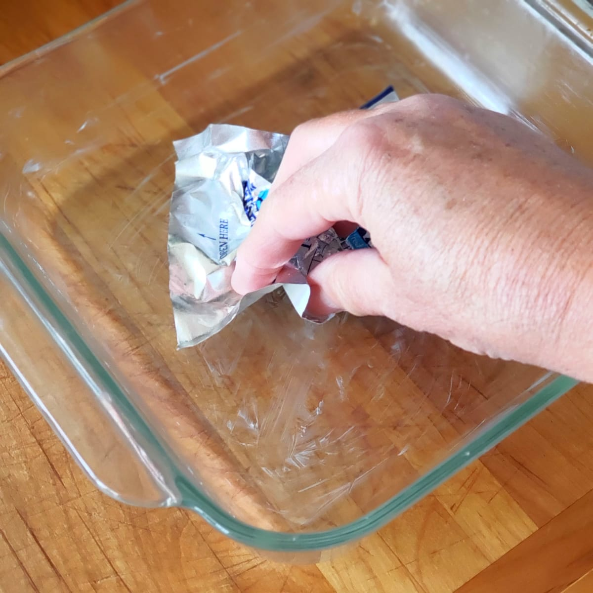 A hand holding the butter wrapper greases the glass baking dish on ShockinglyDelicious.com