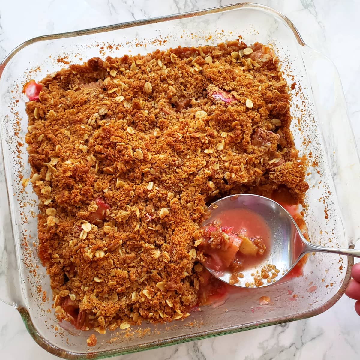 Rhubarb Crumble in a square glass baking dish with a large spoon and a corner of the crumble removed