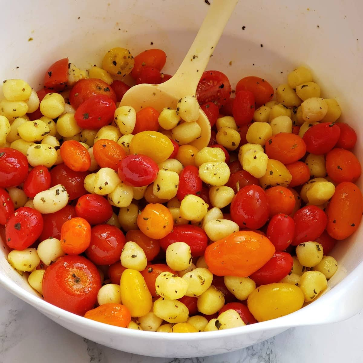 Tomatoes, Gnocchi and seasonings in a white mixing bowl