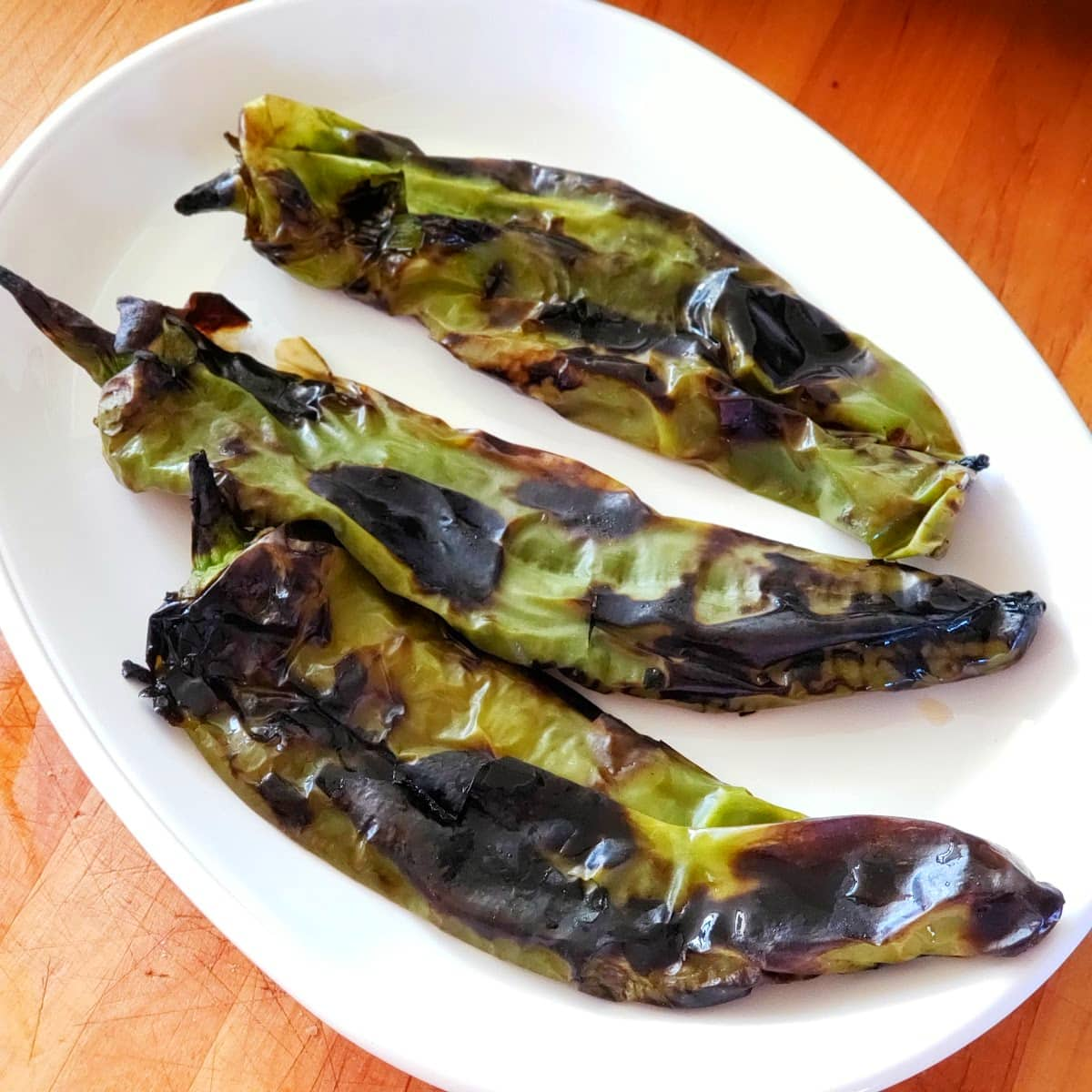 3 roasted Hatch chiles on a white plate on ShockinglyDelicious.com