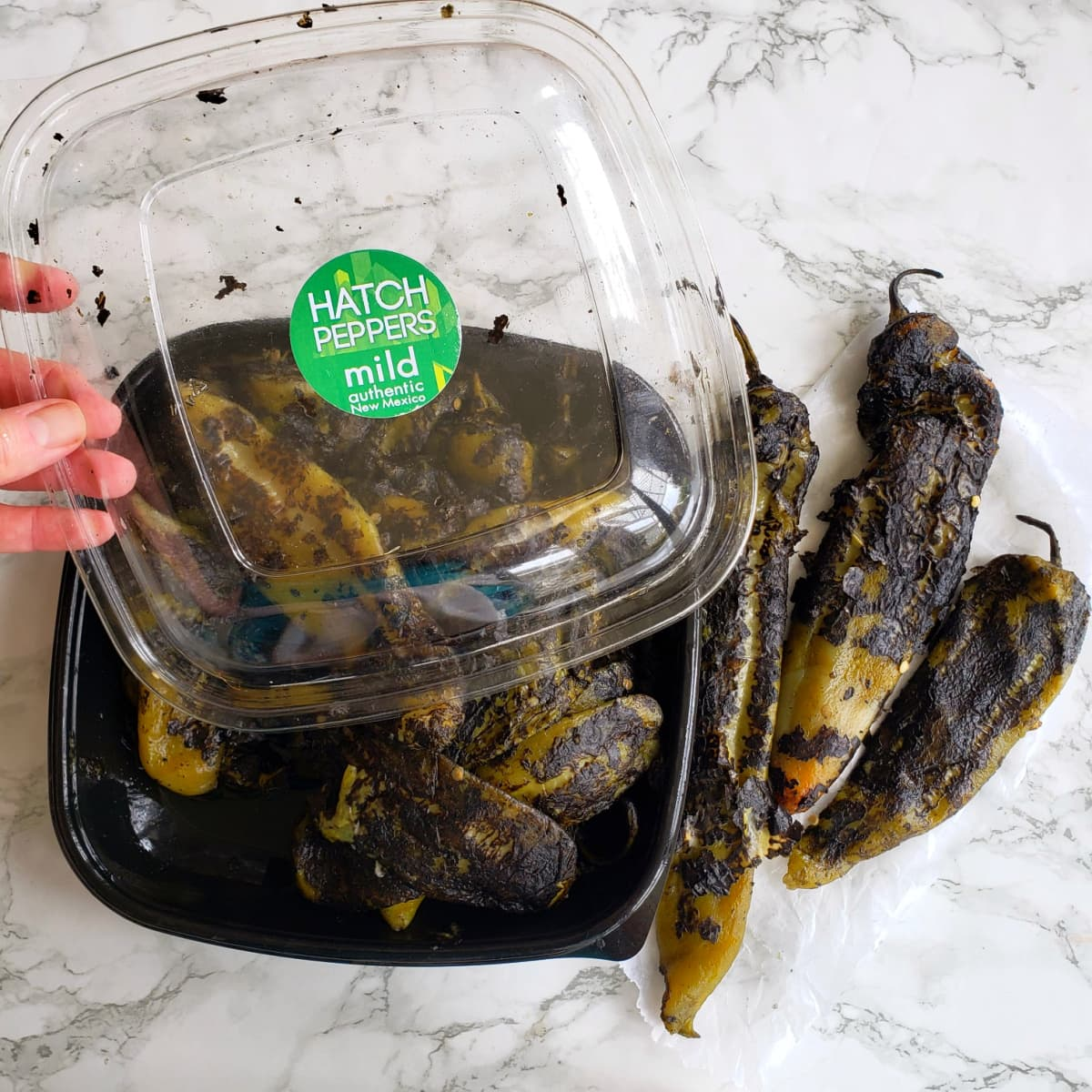 Roasted Hatch chile peppers in a black clamshell package on a white marble counter on ShockinglyDelicious.com